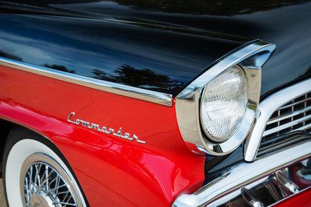 WESTLAKE, TEXAS - OCTOBER 17, 2015: Red and black 1956 Studebaker Commander Sedan classic car. Closeup of headlight details.