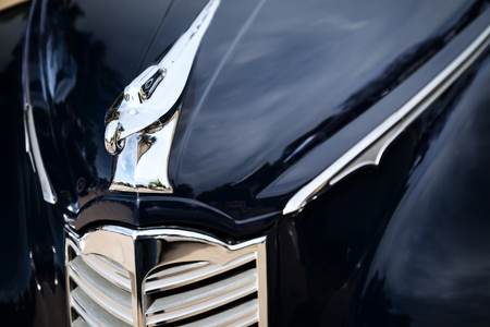 grille: WESTLAKE, TEXAS - OCTOBER 17, 2015: Front closeup with hood ornament of a dark blue 1947 Packard Custom Coupe classic car.