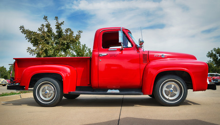 side view: WESTLAKE, TEXAS - OCTOBER 17, 2015: Side view of a red 1955 Ford F-100 pickup truck classic car.