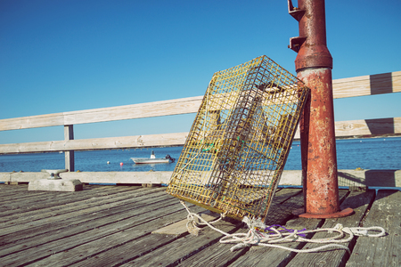 lobster boat: Lobster trap at a fishing pier in coastal Maine, New England. Blue sky with copy space. Stock Photo
