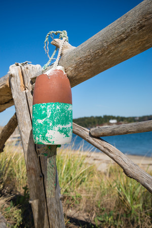 faded: Old weathered lobster buoy hanging on wood fence Stock Photo