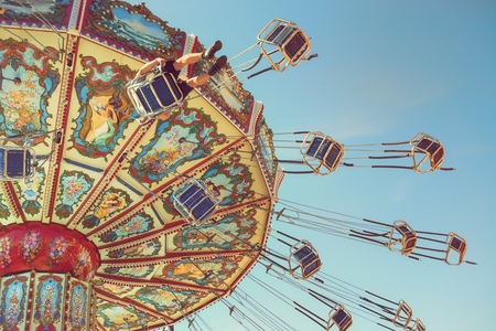 Wave Swinger ride against blue sky, vintage filter effects