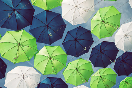 Group of green, blue, and white umbrellas against blue sky 스톡 콘텐츠