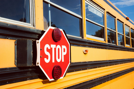 public school: Stop sign with red lights on the side of the school bus Stock Photo