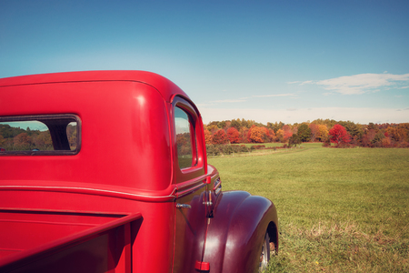 yellow apple: Old red farm truck against apple orchard and autumn landscape background. Vintage filter effects.