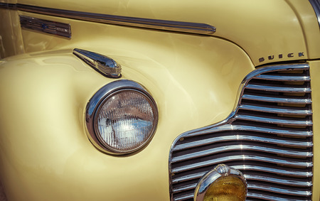 WESTLAKE, TEXAS - OCTOBER 17, 2015: Side view of a yellow 1940 Buick Special 46C Convertible classic car. Closeup of headlight details. Editorial