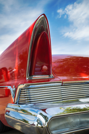 taillight: WESTLAKE, TEXAS - OCTOBER 17, 2015: Tail fin and taillight details of a red 1957 Lincoln Premiere classic car.