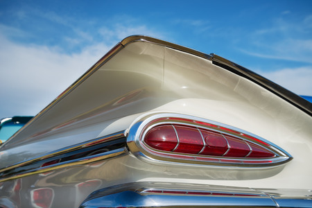 chevrolet: WESTLAKE, TEXAS - OCTOBER 17, 2015: Tail fin and taillight details of a white 1959 Chevrolet Impala Convertible classic car.