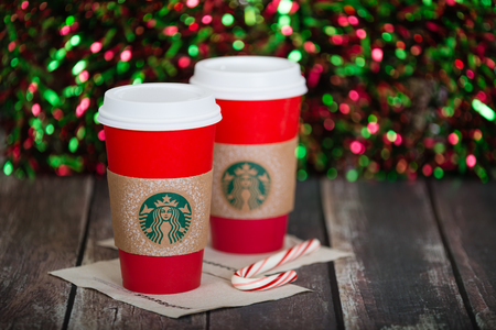 red glittery: DALLAS, TX - NOVEMBER 21, 2015: A cup of Starbucks popular holiday beverage, served in the new 2015 designed red holiday cup. Displayed against dark rustic table and sparkly holiday background. Editorial