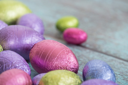 wooden color: Pastel color Easter chocolate eggs on vintage green wooden background, shallow depth of field Stock Photo