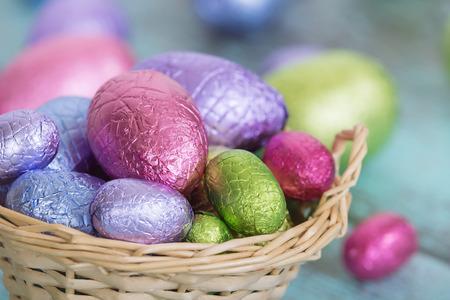 pascuas navide�as: huevos de chocolate de color pastel de Pascua en una cesta, primer con la profundidad de campo