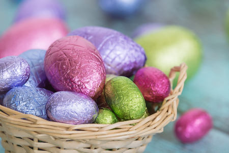 Pastel color Easter chocolate eggs in a basket, closeup with shallow depth of field
