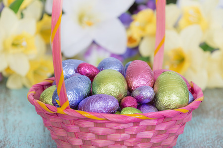 Pastel color chocolate eggs in a pink Easter basket, spring flowers in the background
