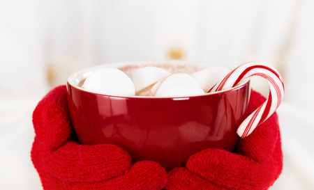 Red gloved hands holding a red cup of hot chocolate with marshmallows and a candy cane. Stock Photo