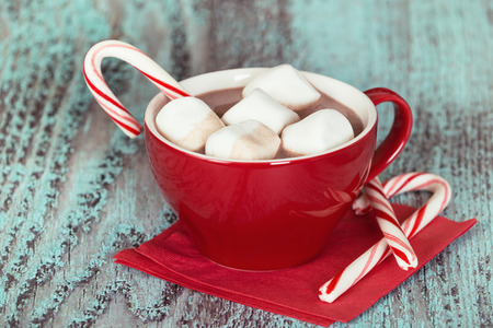 chocolate candy: Hot chocolate with marshmallows and candy cane in a red cup. Vintage green background. Shallow depth of field.