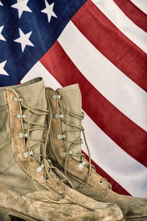shoe string: Old combat boots with American flag in the background. Vintage filter effects. Stock Photo