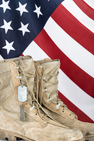 combat boots: Old combat boots and dog tags with American flag in the background
