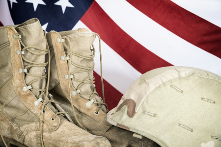combat boots: Old combat boots and helmet with American flag in the background Stock Photo