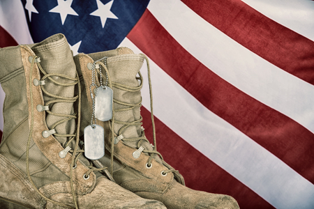 Old combat boots and dog tags with American flag in the background. Vintage filter effects.