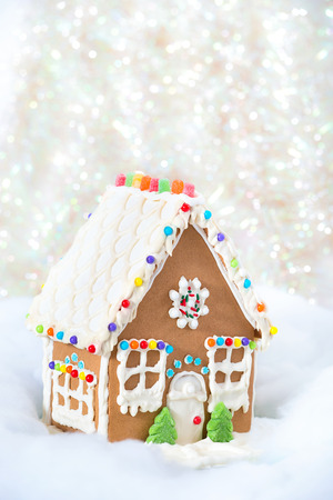 holiday house: Christmas Gingerbread House displayed against snowy and glittery holiday background. Copy space.