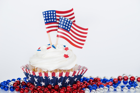 Patriotic cupcake with decorative American flags and red, white, and blue beads against white background 版權商用圖片 - 77087815