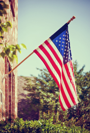 Patriotic American flag hanging in front of a home. Blue sky with copy space. Vintage filter effects.