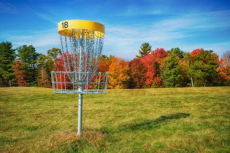 Disc golf hole basket in an autumn park