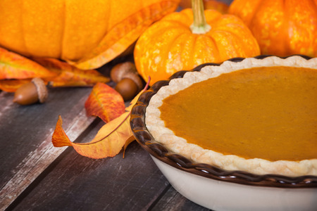 Pumpkin pie with pumpkins, golden autumn leaves, and acorns, on rustic table