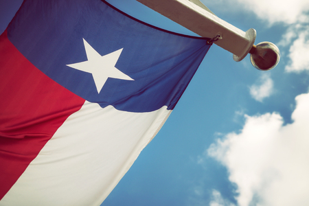 State flag of Texas waving in the wind on a sunny day, closeup. Blue sky with white clouds background.