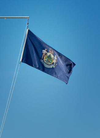 State flag of Maine waving in the wind on a flagpole. Blue sky background with copy space. Stock Photo