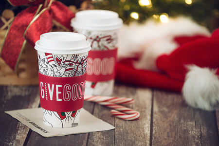 Dallas, TX - November 4, 2017: Starbucks popular holiday beverage, served in the new 2017 designed holiday cups. Displayed with candy canes on wooden rustic table. Christmas hats and sparkling tree lights in the background.