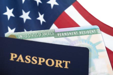 Cartão de residente permanente dos Estados Unidos da América, cartão verde, exibido com uma bandeira dos EUA no fundo e um passaporte em primeiro plano. Conceito de imigração. Feche a profundidade de campo. Foto de archivo - 90296729