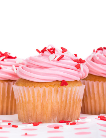 Pink Valentines Day cupcake with red and white heart shape sprinkles