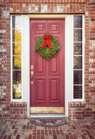 Traditional balsam fir Christmas wreath hanging on a red door of a brick house Banco de Imagens