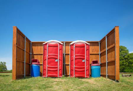 Two red portable restrooms and trash cans with a wood fence around them in a park. Trees and blue sky background.