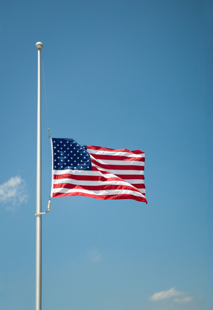 The United States flag flying at half-mast or half-staff on a flagpole. Blue sky background with copy space.