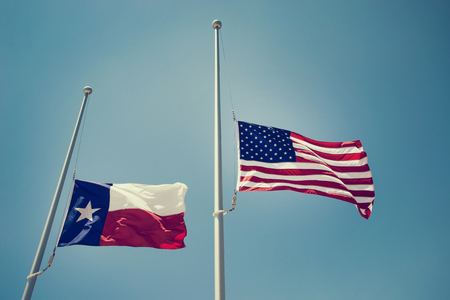The state flag of Texas and the United States flag flying at half-mast or half-staff on a flagpole. Blue sky background with copy space. Vintage filter effects. Stock Photo