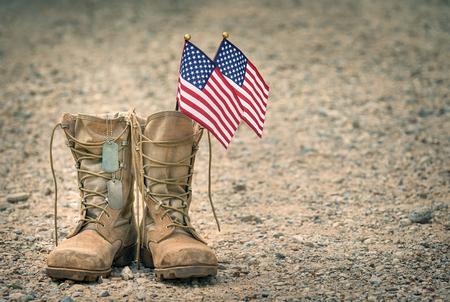 Anciennes bottes de combat militaires avec plaques d'identité et deux petits drapeaux américains. Fond de gravier rocheux avec espace de copie. Memorial Day ou concept de jour des anciens combattants.