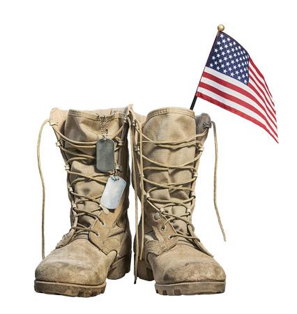 Viejas botas militares de combate con la bandera estadounidense y placas de identificación Foto de archivo