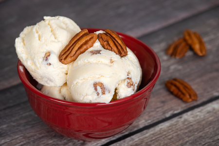 Delicious butter pecan ice cream served in a red bowl. Фото со стока