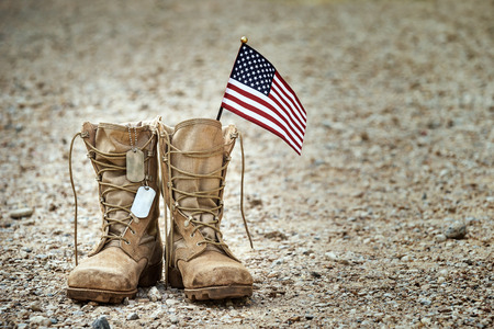 Old military combat boots with dog tags and a small American flag.