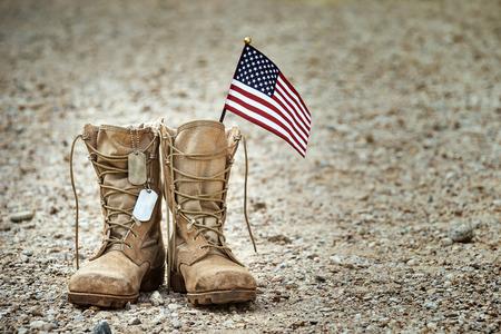 Viejas botas militares de combate con placas de identificación y una pequeña bandera estadounidense.