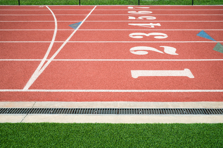 Red running track, track and field or athletics track finish start line with lane numbers