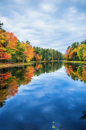 Fall foliage colors reflected in still lake water on a beautiful autumn day in New England 免版税图像 - 132557756