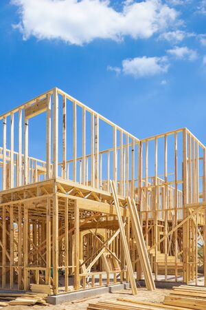 New residential construction home framing. Blue sky and white clouds background. Stock Photo