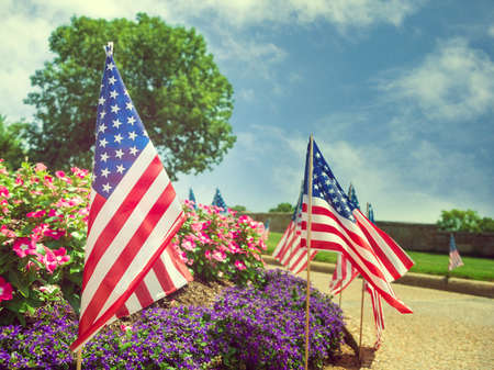 American flags displayed on the side of the street in honor of the 4th of July. Beautiful flower bed and blue sky background. Stock Photo