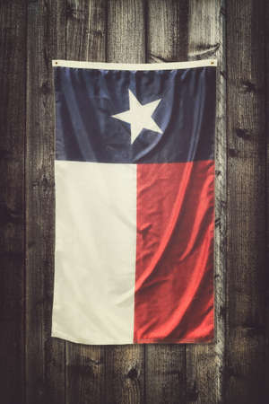 Texas state flag hanging on wooden board background. Vintage filter effects.