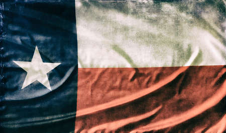 Texas State Flag on waving old fabric texture. Vintage filter effects for weathered look.