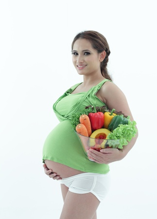 Pregnant woman holding a bowl of salad. photo