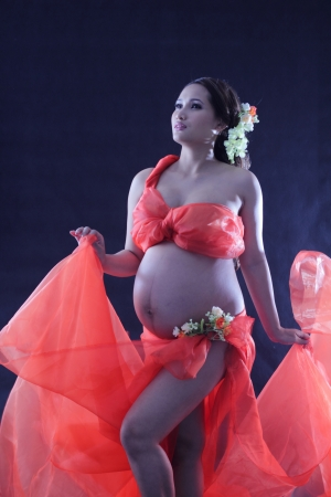 Pregnant woman wearing a red floral decoration. photo